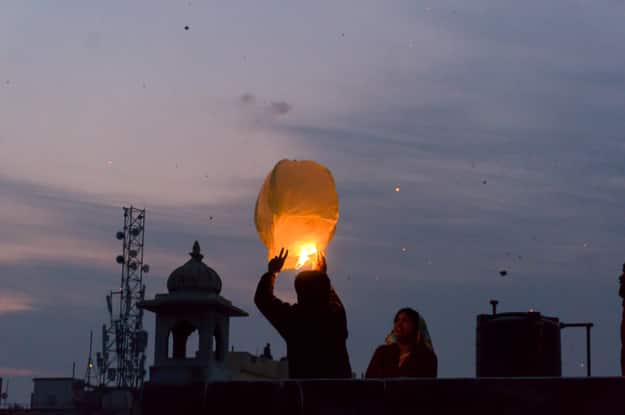 People release a chinese lantern into the air as part of Makar Sankranti or Uttaryan celebration in Rajasthan