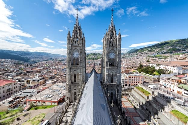 View of the towers of the Basilica in Quito, Ecuador with the city visible in the background