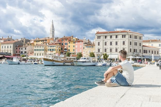 young man relaxing sitting at the old harbor with fishing boats of Rovinj during a cloudy summer day, a bright panoramic view at Rovinj Croatia Istria Europe