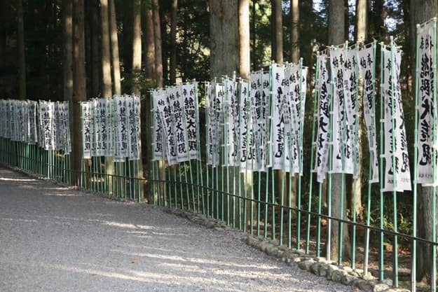 An image of Kumano Kodo, a sacred trail and World Heritage site in Wakayama, Japan. Letters on the banners say Kumano Daigongen, the name of the god