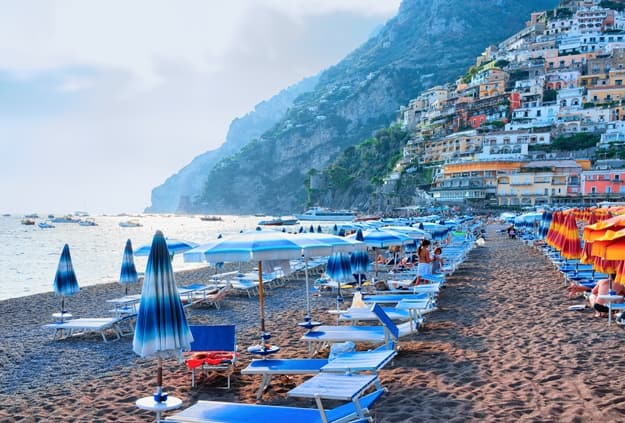 Beach with umbrellas in Positano town and Tyrrhenian sea, Amalfi coast