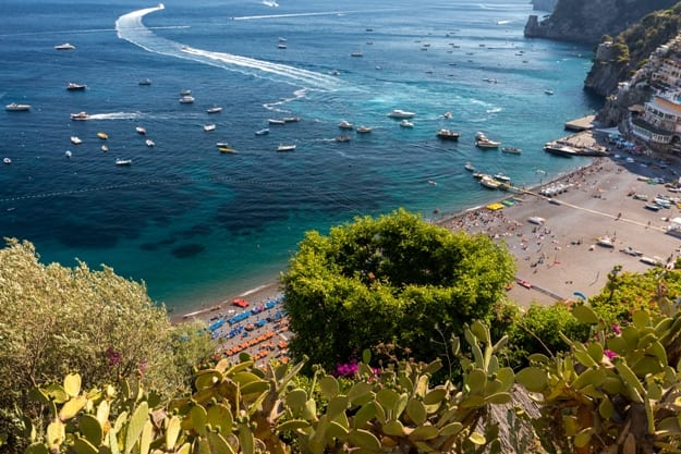 The main beach in Positano, Spiaggia Grande, with its bright orange and blue beach umbrellas and the sparkling blue sea of the Amalfi Coast