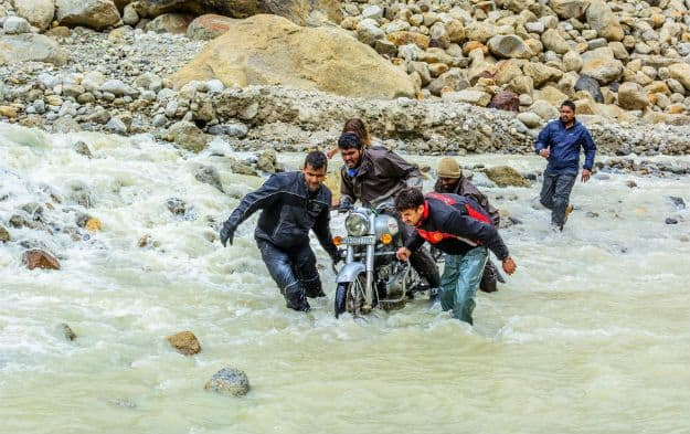 Bikers helping each other through water crossing