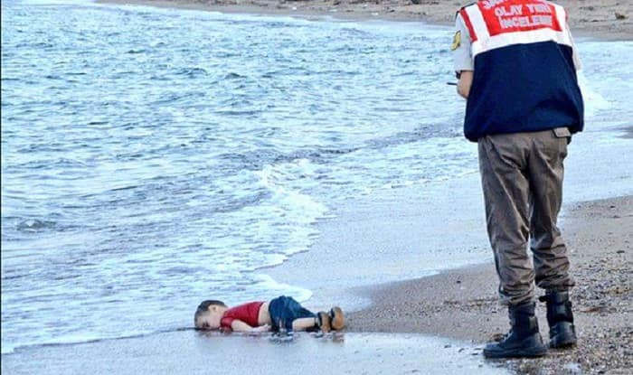 Humanity Washed Ashore: Drowned Syrian toddler's body being taken by policeman (Watch Video)