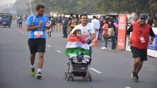 New Delhi Marathon: This man ran 21 kms pushing his little daughter in a stroller with a message