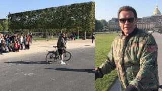 Arnold Schwarzenegger photobombs Thai tourists posing in front of Paris' Eiffel Tower