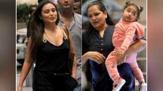 Rani Mukerji is all smiles for the paparazzi, while her daughter Adira is fascinated with all the attention - view airport pics