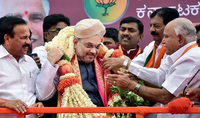 Amit Shah being welcomed by state unit chief B S Yeddyurappa (right) [Image: PTI]