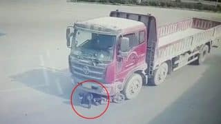 Shocking Video: Female Biker Hit by Truck, Dragged on for Some Distance, Escapes Unhurt in the Accident