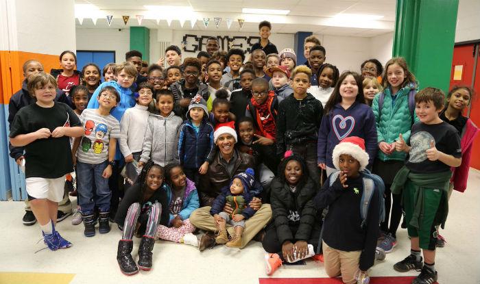 Barack Obama dons Santa hat to deliver Christmas presents to children