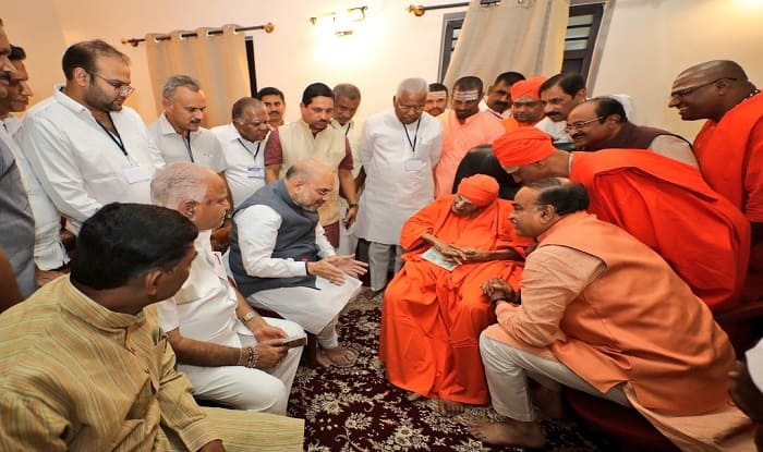 सिद्धगंगा मठ में लिंगायत समुदाय के संत श्री शिवकुमार स्वामी से मिलते अमित शाह. फोटो: ट्विटर