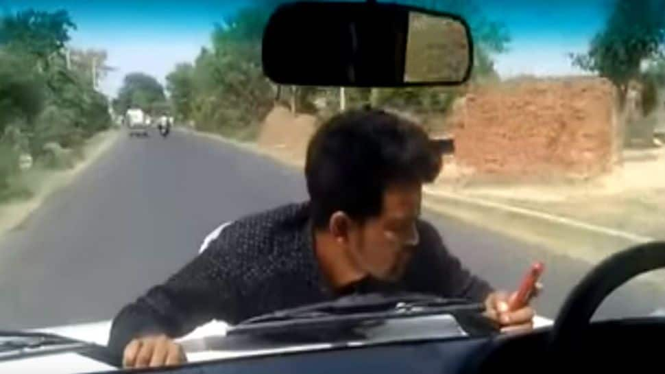 Bizarre: Official drives for 4 km as man clings on to bonnet