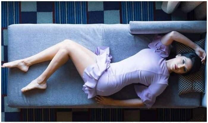 Sunny Leone's Sensuous Picture in Short Lilac Dress Lying on a Sofa Will Make You go Weak in Knees
