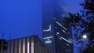योग दिवस के मौके पर योगासन मुद्रा की तस्वीरों से सजी संयुक्त राष्ट्र मुख्यालय की इमारत